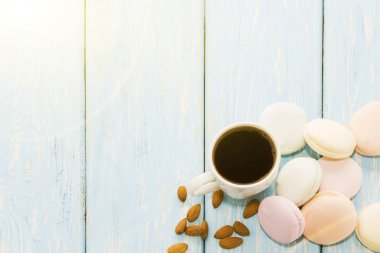 A Cup of coffee with Marshmallows on a light blue background next to almond nuts. Place for text