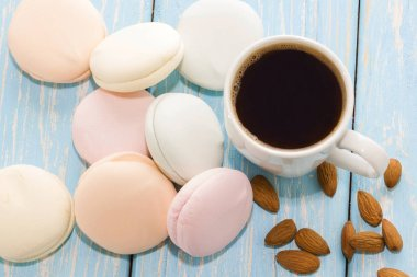 A Cup of coffee with Marshmallows on a light blue background next to almond nuts
