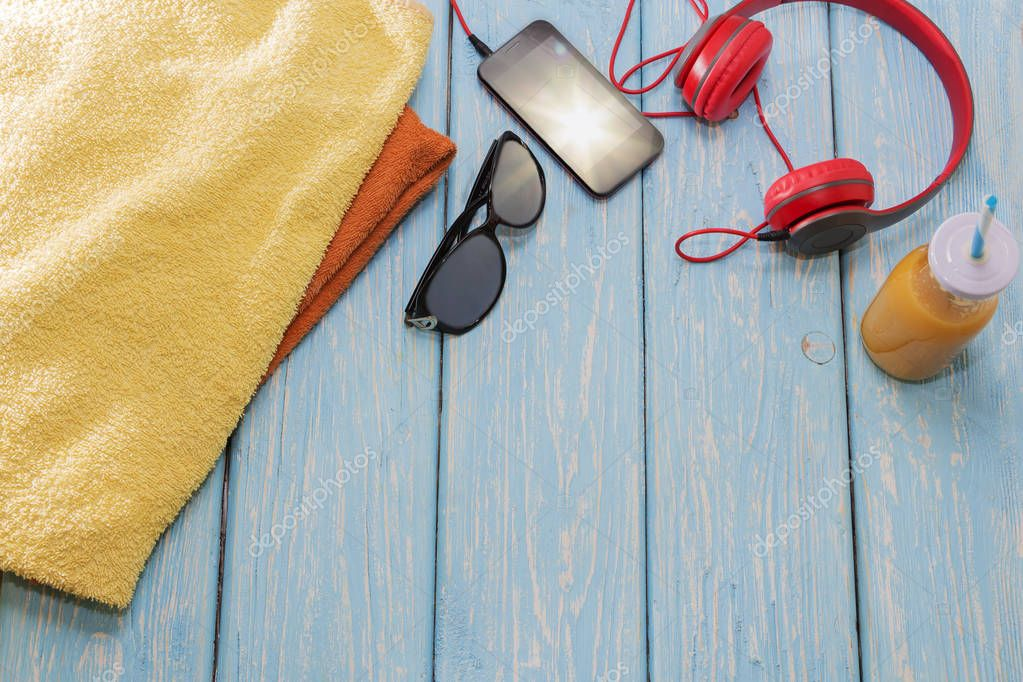 phone with headphones and sunglasses on a blue background, on a summer beach.