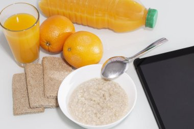 Healty breakfast with muesli, and orange juice. View from above on wooden table with notepad for copy space