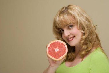 beautiful blonde woman smiling holding grapefruit slice posing on beige studio background