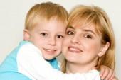 portrét šťastné matky a syna, které představují izolované na bílém