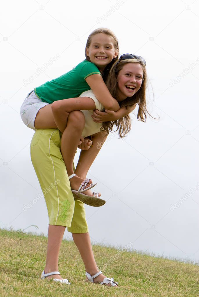 Two young girls with long hair having fun outdoors, full length