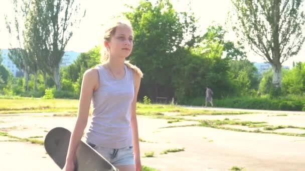 Dospívající dívka chodit s skateboard v letním dni