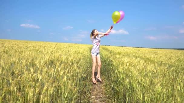 Dospívající dívka s balónky skákání v poli