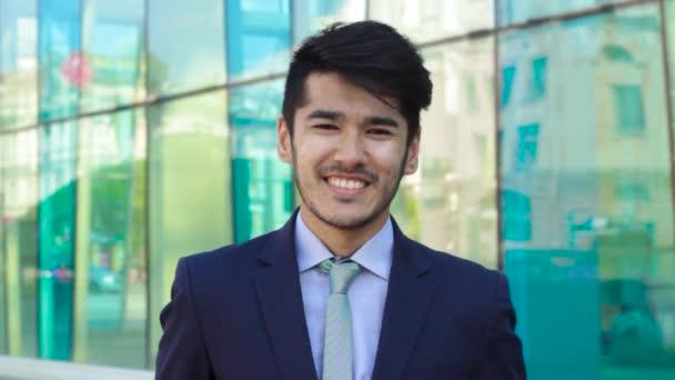 Asijské muž hledá ve fotoaparátu a usmívá se
