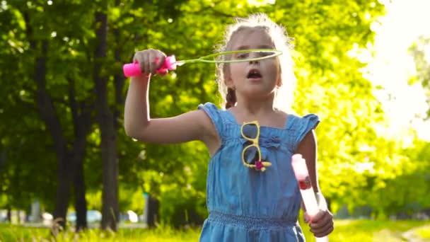 charmantes Mädchen, das mit riesigen Seifenblasen spielt
