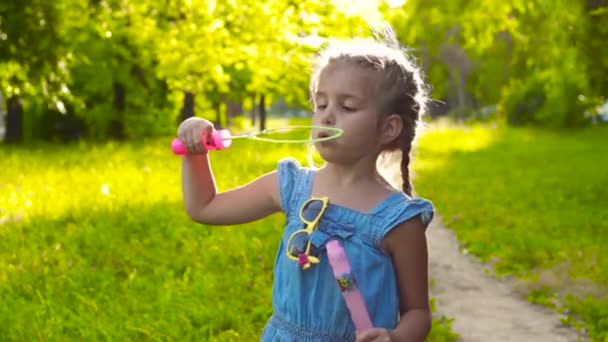 Nettes Mädchen spielt mit riesigen Seifenblasen