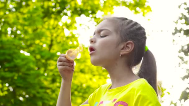 kleines Mädchen im gelben T-Shirt pustet Seifenblasen im Park