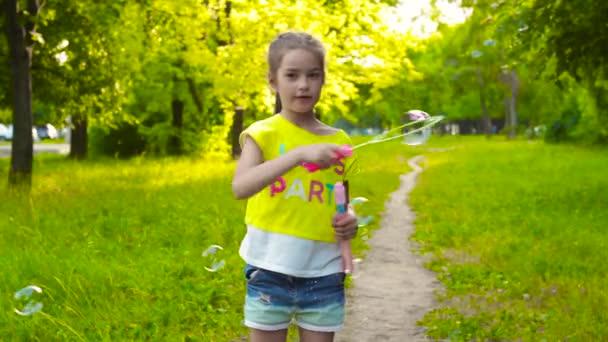 Kleines Mädchen spielt im Sommerpark mit Seifenblasen