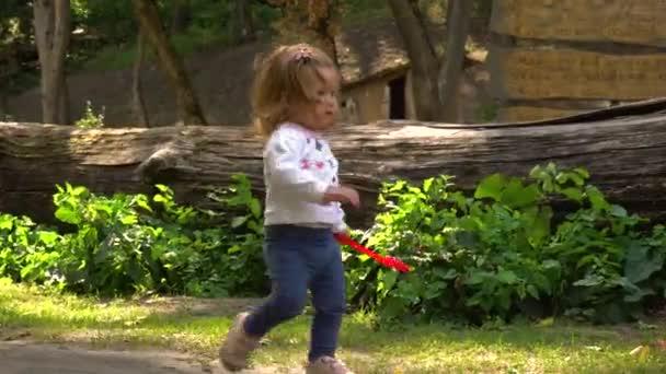 Funny girl with sand shovel walking in park