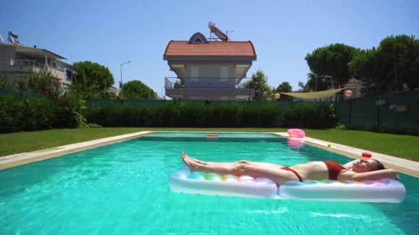 Női barna fürdőruha véve sunbathes felfújható úszó feküdt és napozásra a medence tiszta vízzel