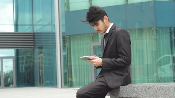 Businessman using tablet for work in front of office center