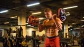Fotografie Kulturista muž dělá cvičení na biceps s činka