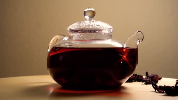 Spinning teapot with red hibiscus tea on table