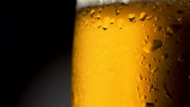 Kézműves világos sör, üveg-, kondenzátum és víz csepp. Forgó át sötét háttér előtt. 4k Uhd