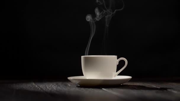 Šálek kávy na tmavém vintage dřevěné pozadí s párou