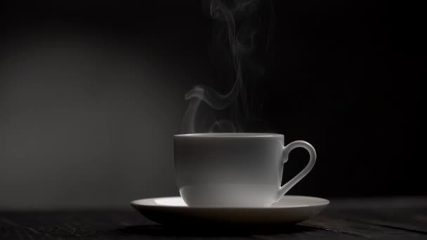 Steam slowly rising from a cup of hot coffe. Dark background