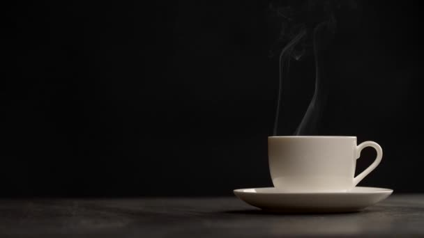 Slow motion shot of steaming cup of coffee over black background