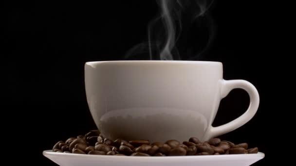 Drehschuss einer Kaffeetasse mit Dampf und Kaffeebohnen. Zeitlupe, schwarzer Hintergrund
