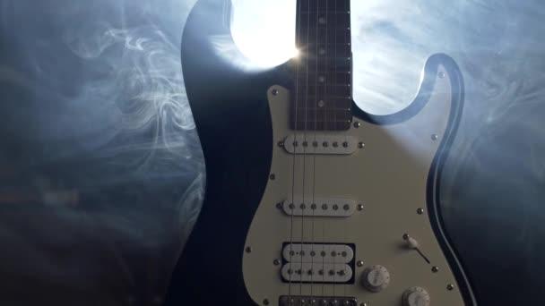 Elektrická kytara na jevišti v podhledech lehké a kouře před rockový koncert