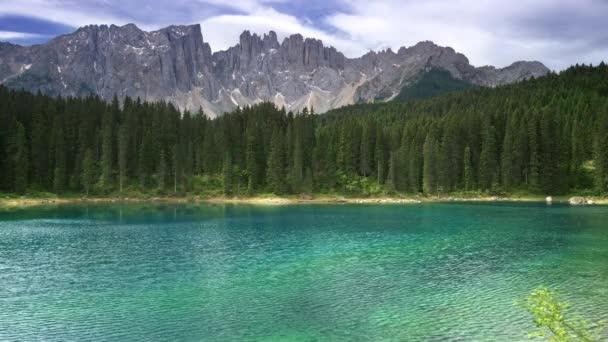 Karersee jezero nebo Lago di Carezza, Itálie. Vítr fouká na vodách jezera. Borovicový les a hory Dolomity jsou v pozadí. UHD