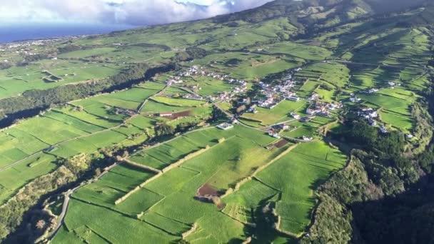 Ostrov Sao Miguel, Azory, Portugalsko. Vesnice a zelená pole během za jasného slunečného dne. Letecký snímek, Uhd