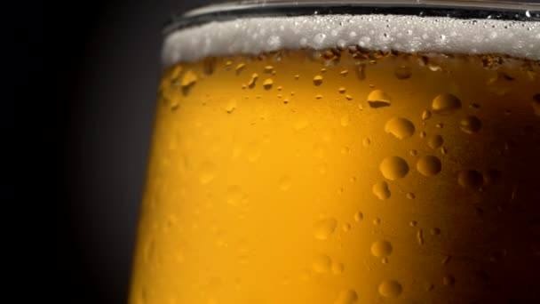 Pivo hrnek detail. Mokrý, otočná skla naplněné zlaté barvy chlazený, pěnivý nápoj na tmavém pozadí. Poutavé, názorné a chutný reklama jako výstřel. 4k
