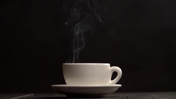 Kouřící horký šálek kávy. Pára z bílý šálek na černém pozadí. Zpomalený záběr