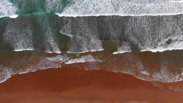 Ocean pobřeží pozadí. Pěnivý vlny tyrkysového oceánu do hnědá písková pláž. Shora dolů výstřel, Uhd