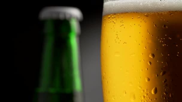Rotující Zlaté pivo sklo pokryté kapky vody. Zelené pivo láhev na pozadí. Zblízka střílel, 4k