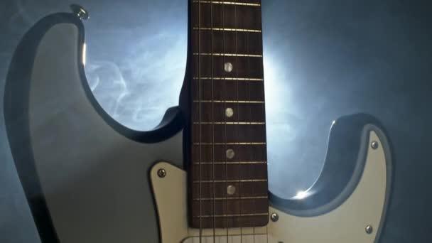 Ragyogó elektromos gitár a füst. Közeli lövés a hátsó fény, Uhd