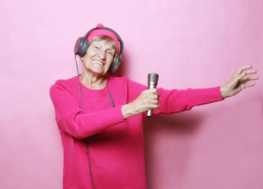 Funny old lady listening music with headphones and singing with mic over pink background