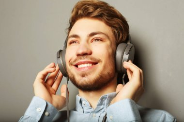 life style, happiness, emotional and people concept: Enjoying his favorite music. Happy young stylish man adjusting his headphones ad smiling