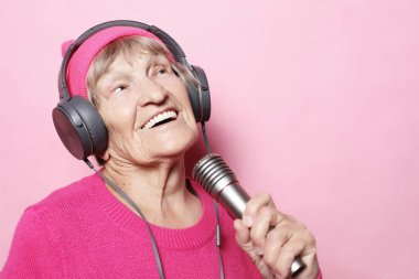 Happy grandmother with headphones and microphone