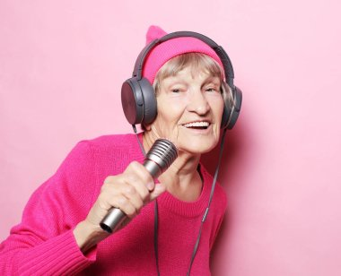 lifestyle and people concept: Funny old lady listening music with headphones and singing with mic over pink background