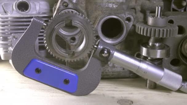 Průmyslový stále žije mikrometr na pozadí podrobností o automobilech a mechanismech. Panenka