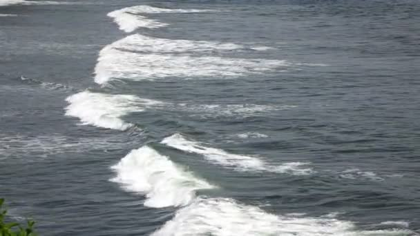 The coast of the tropical sea in sunny day, Waves run on the coast with black stones,Slow Motion