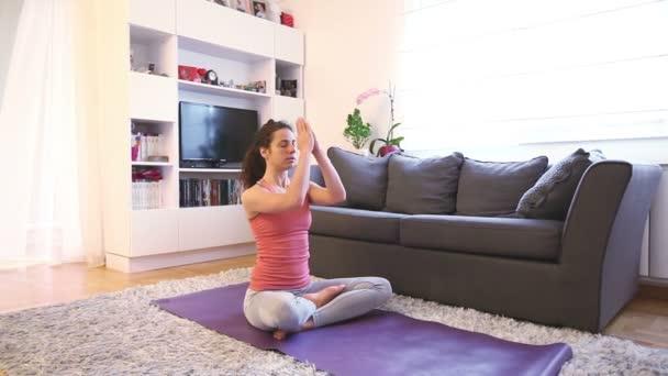 Mladá žena medituje, cvičí jógu, lotus pose, ardha padmasana cvičení, relaxaci a odpočinek, zdravý životní styl