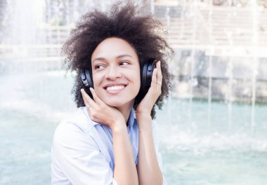 Portrait of Beautiful Happy Black Young Woman With Afro Hair Style Listening Music with wireless headphones outdoor