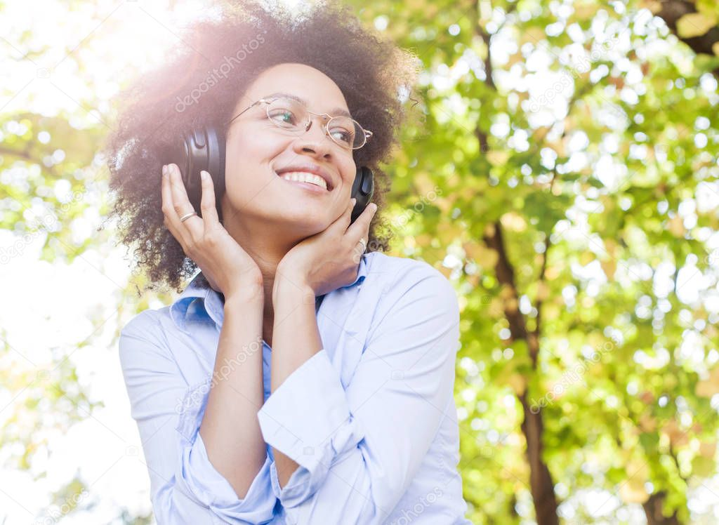 Portrait of Beautiful Happy Afro American Young Woman Listening Music In Nature