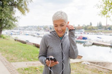 Portrait Of Active Senior Running Woman Listening Music With Smartphone, Workout Outdoor.
