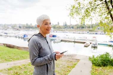 Portrait Of Active Senior Running Woman Listening Music With Smartphone In Nature, Workout Outdoor.