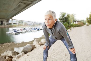 Active Senior Running Woman Resting After Jogging  Listening Music With Smartphone On River Shore , Workout Outdoor.