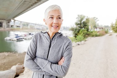 Portrait Of Smiling Senior Woman With Earphones Listening Music After Fitness Exercise
