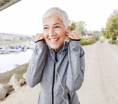 Happy Senior Woman With Earphones Listening Music After Fitness Exercise. Workout Outdoor