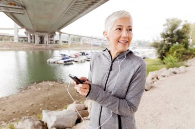 Senior Woman Relax Listening Music With Smartphone After Running, Gray-Short Hair, Wear Sports clothes ,Workout Outdoor.