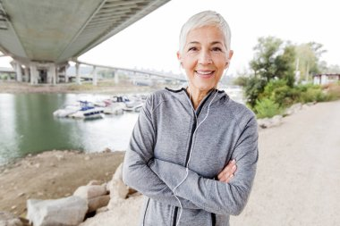Smiling Senior Woman Relax Listening Music With Earphones After Running, Gray-Short Hair, Wear Sports clothes ,Workout Outdoor.