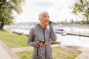 Portrait Of Senior Woman Listening Music After Running At River Shore , Mature Woman Workout Outdoor.
