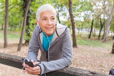 Healthy Senior Woman Relax Listening Music With Phone After Jogging In Forest. Fit Lifestyle Mature People Workout Outdoor.